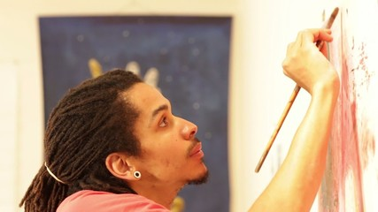 Mixed race artist painting in his studio
