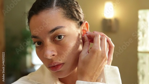 Mixed race woman putting earrings on