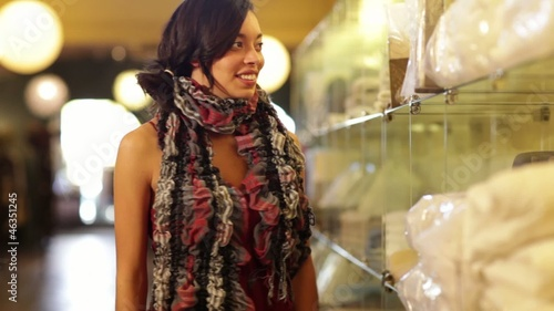Mixed race woman looking at linens in boutique