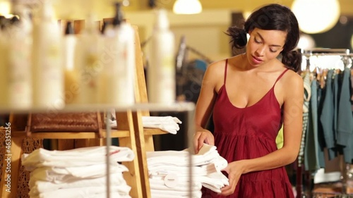 Mixed race woman shopping for linens in boutique