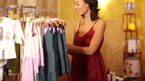 Mixed race woman looking at children's clothes in boutique