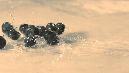 Blueberries roll across marble surface (slow motion)