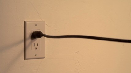 Plug is pulled, with sparks, from wall socket (slow motion)