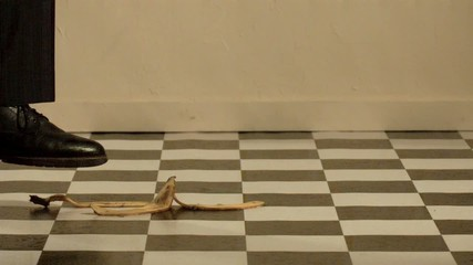 A man steps on banana peel and falling (slow motion)