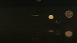 Coins falling onto black granite (slow motion)