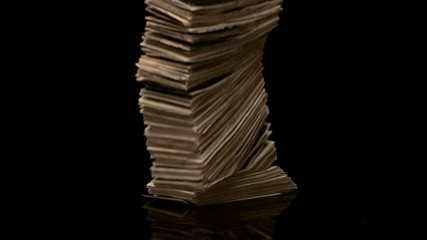 Stack of money falling onto black granite (slow motion)