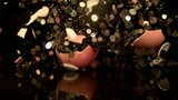 Piggy bank full of coins exploding (slow motion)