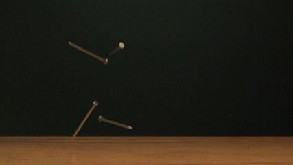 Nails falling onto board (slow motion)