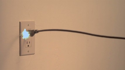 Power cord snakes into the frame and plugs into the wall socket  with sparks (slow motion)