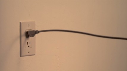 Power cord snakes into the frame and plugs into the wall socket (slow motion)