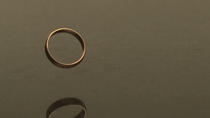 A gold ring falling through the air, bouncing and spinning on granite surface (slow motion)