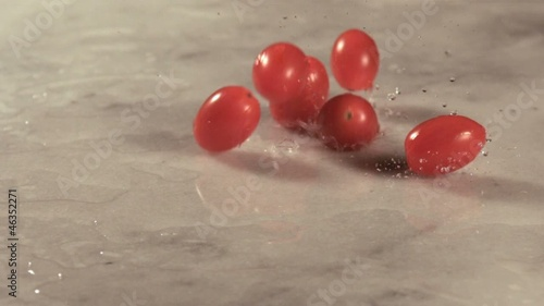 Cherry tomatoes falling onto marble surface (slow motion)