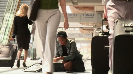Business traveler searching through clothes on airport floor