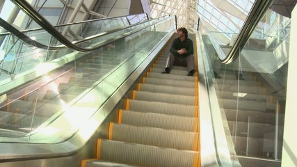Caucasian businessman sitting on ascending escalator