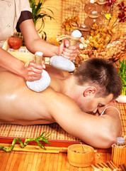Man getting herbal ball massage treatments .