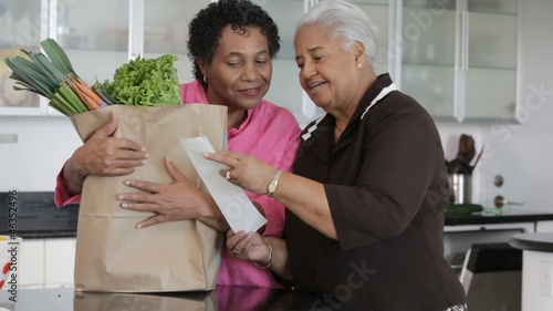 African American mother and daughter looking at groceries in kitchen