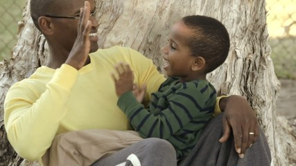 African American father siting with son in his lap