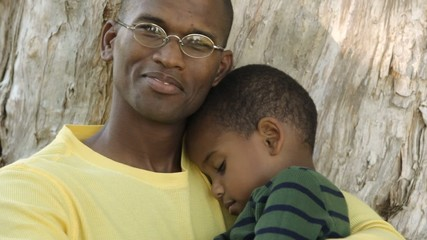 African American father comforting son
