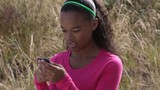 Mixed race girl text messaging on cell phone