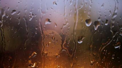 Lights glowing though rain dripping down glass