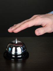 Hand ringing in service bell on wooden table on black