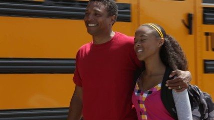 Father and daughter walking near school bus