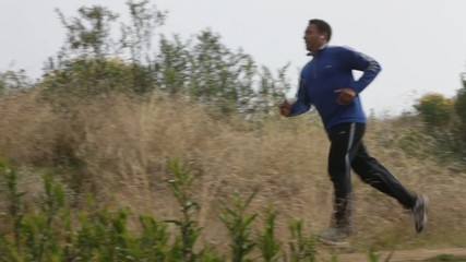 Mixed race man jogging in remote area listening to music