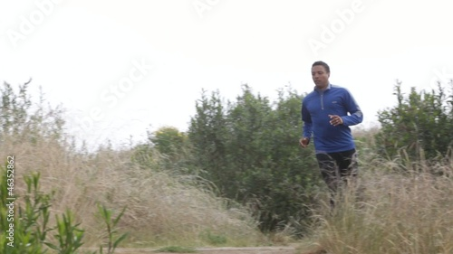 Mixed race man jogging in remote area