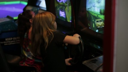 Girls playing video games in arcade