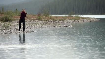 Caucasian woman fishing on a mountain lake