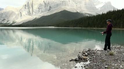 Woman fishing on a mountain lake