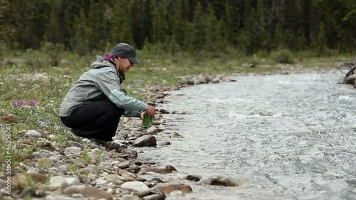Caucasian woman filling water bottle from stream