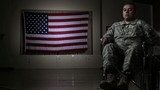 Hispanic soldier in wheelchair with missing left arm in front of American flag