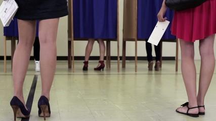 Legs of voters who are holding ballots in front of voting booths