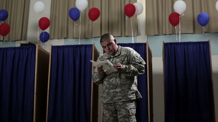 Hispanic soldier in front of voting booths