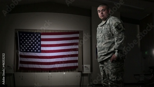 Hispanic soldier in voting hall in front of flag