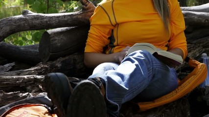 Hispanic woman taking a break from a hike to read