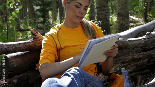 Hispanic woman taking a break from a hike to draw
