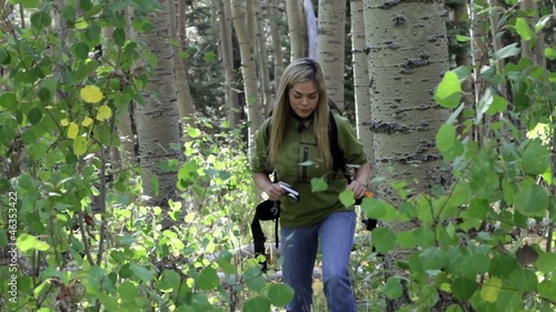 Hispanic woman taking photos on hike in the woods