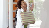 African American woman with shopping bags window shopping
