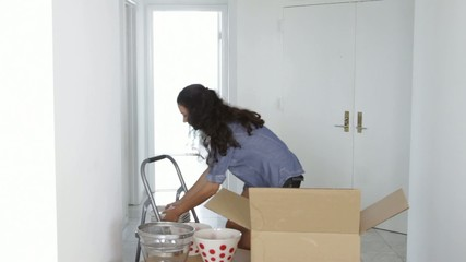 Latin woman unpacking dishes