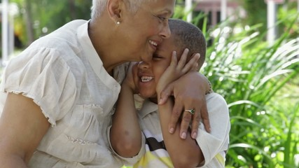 African American grandmother telling grandson a secret