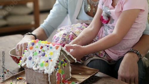 Caucasian mother and daughter making a gingerbread house