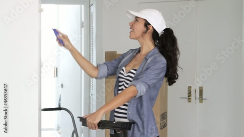 Latin woman painting wall