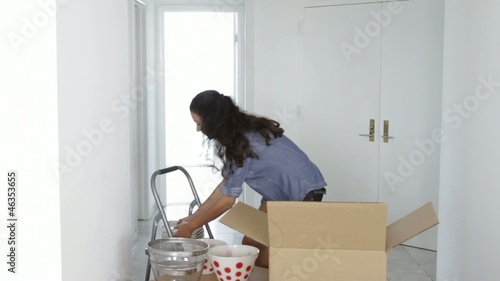 Latin woman unpacking dishes