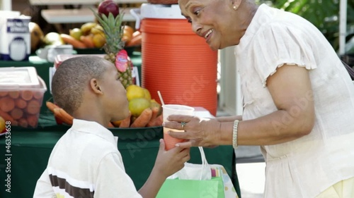 African American grandmother giving grandson orange juice