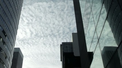 Clouds moving slowly across sky between two tall buildings