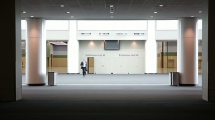 Black businessman running through empty convention center
