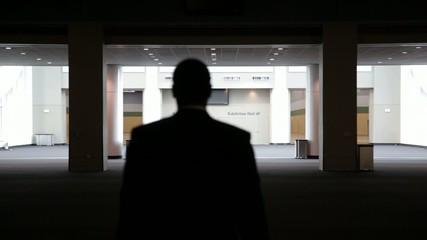 Black businessman walking through empty convention center