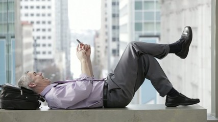 Caucasian businessman laughing while laying on a bench text messaging on cell phone